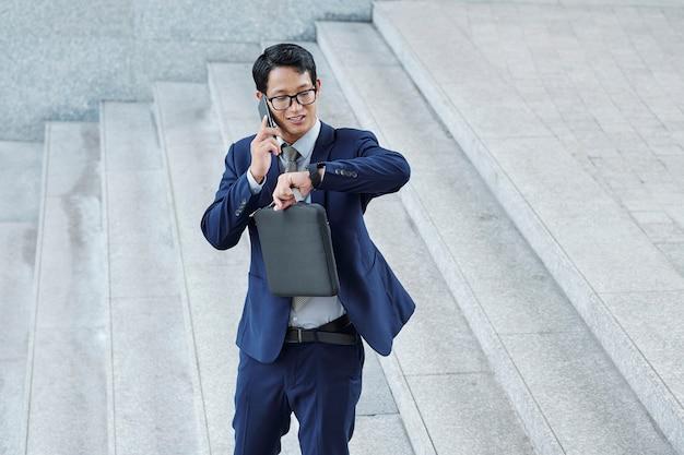 Hübscher positiver junger asiatischer unternehmer, der zeit auf seiner armbanduhr überprüft, wenn er mit kollegen am telefon spricht