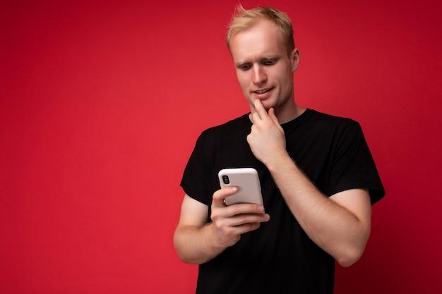 Hübscher positiver junger blonder mann isolierte wand mit schwarzem t-shirt