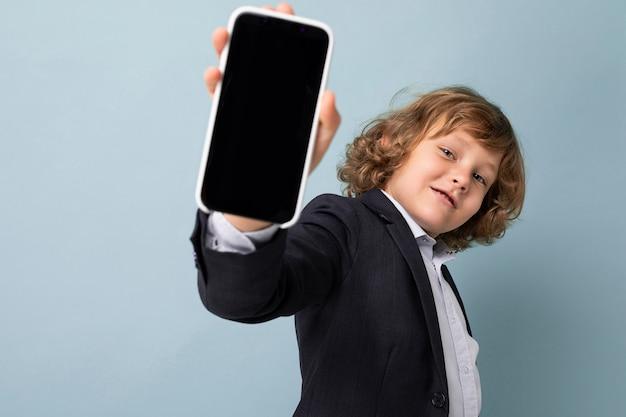 Hübscher positiver lächelnder junge mit dem lockigen haar, der anzug trägt, der das telefon lokalisiert über blauem hintergrund hält, der kamera betrachtet und smartphone mit leerem bildschirm zeigt. modell, ausschnitt
