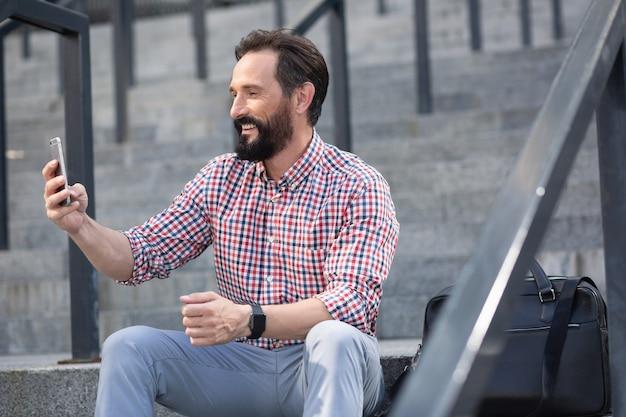 Hübscher positiver mann, der sein telefon benutzt, während er draußen auf der treppe sitzt