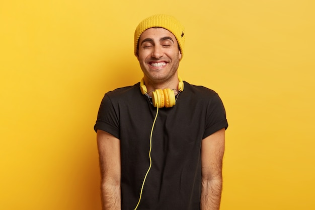Hübscher positiver mann mit kopfhörern am hals, lächelt breit und schließt vor vergnügen die augen, trägt hut und schwarzes t-shirt