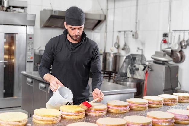 Hübscher professioneller konditor, der einen stapel köstlichen kuchen in der konditorei macht.