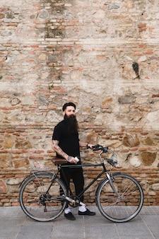 Hübscher radfahrer, der mit fahrrad steht