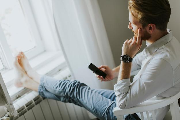 Hübscher redhair mann schreibt eine mitteilung am telefon