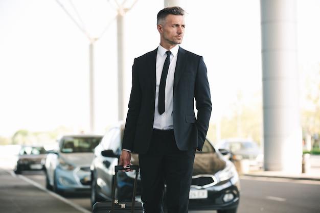 Hübscher reifer geschäftsmann, der ein taxi fängt
