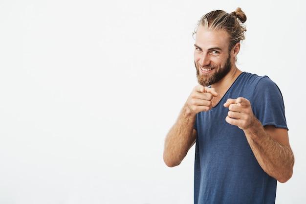 Hübscher reifer kerl mit bart, der mit zeigefingern auf beiden händen mit glücklichem ausdruck auf kamera zeigt