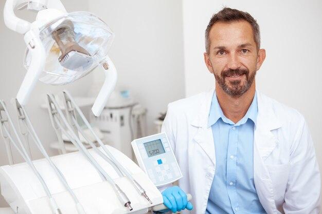 Hübscher reifer männlicher zahnarzt, der fröhlich zur kamera in seinem büro lächelt
