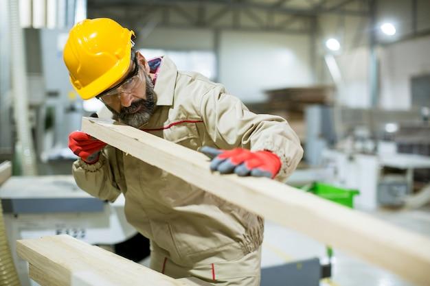 Hübscher reifer mann, der in der möbelfabrik arbeitet