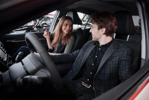Hübscher reifer mann, der seine frau anlächelt, während sie zusammen in ihrem neuen auto sitzen