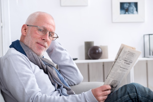 Hübscher reifer mann, der zeitung auf sofa liest