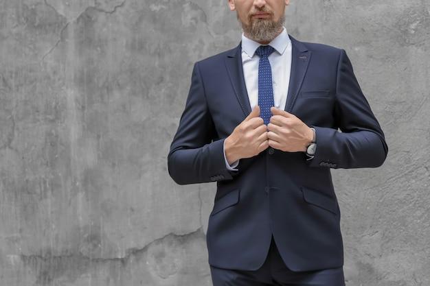 Hübscher reifer mann im eleganten anzug auf grau