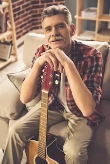 Hübscher reifer mann in der zufälligen kleidung hält eine gitarre.