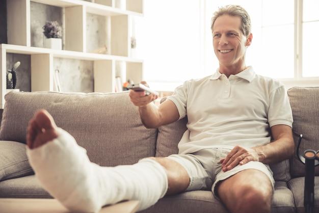 Hübscher reifer mann mit dem gebrochenen bein im gips.