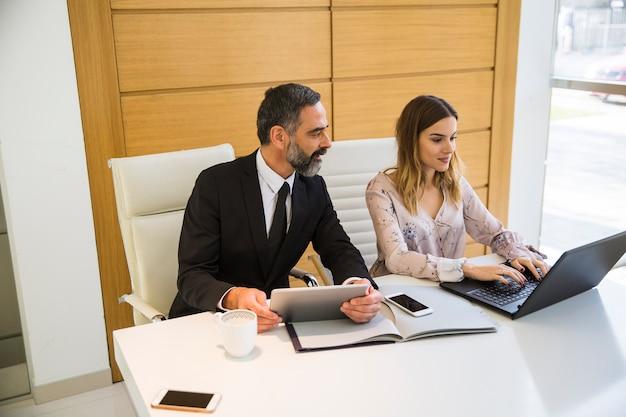 Hübscher reifer mann mit digitaler tablette und geschäftspartner der jungen frau mit laptop, der im büro arbeitet