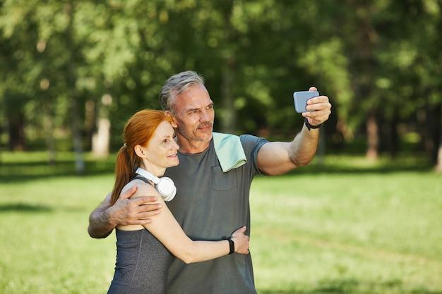 Hübscher reifer sportler mit handtuch auf schulter, das frau umarmt und selfie mit ihr nach dem training im park nimmt