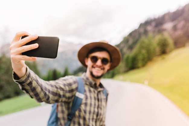Hübscher reisender, der auf italienischer naturlandschaft aufwirft und lächelt, aktiven urlaub genießt