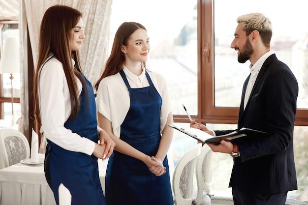 Hübscher restaurantmanager spricht mit kellnerinnen über arbeitsprozeß