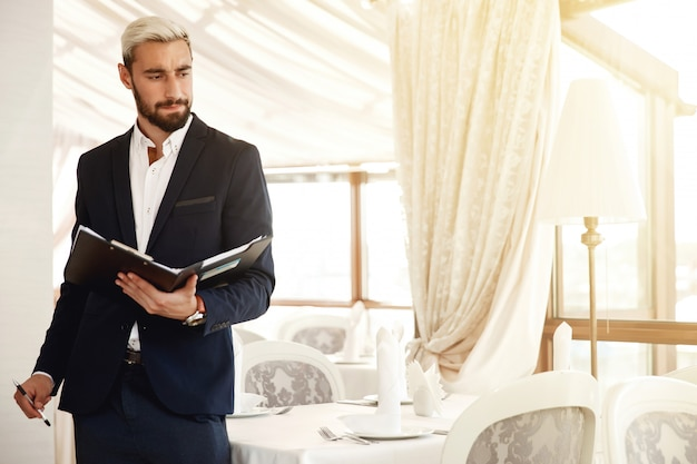 Hübscher restaurantmanager steuert den arbeitsprozeß