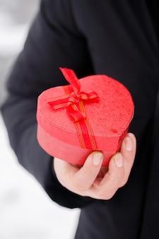Hübscher romantischer junger mann mit roter herzförmiger schachtel