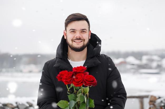 Hübscher romantischer junger mann mit strauß roter rosen in den händen