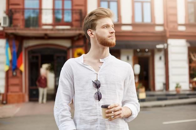 Hübscher rothaariger bärtiger mann mit stilvollem haarschnitt im weißen hemd, das durch stadt geht und kaffee am morgen vor hartem arbeitstag trinkt.