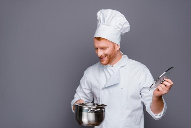 Hübscher rothaariger koch, der gegen die graue wand aufwirft