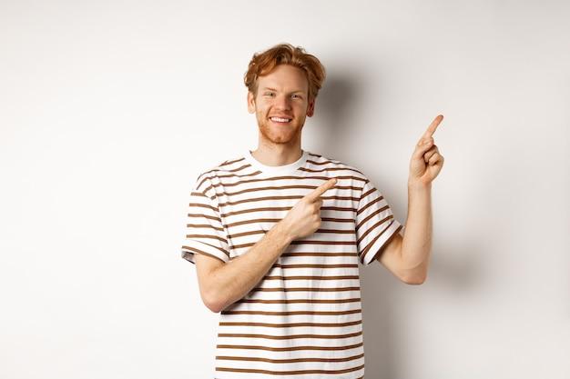 Hübscher rothaariger mann, der logo zeigt, finger nach rechts zeigt und lächelt und über weißem hintergrund steht.