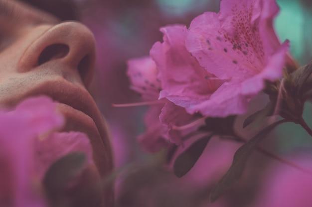 Hübscher ruhiger mann mit blumen in seinem mund. leute-, gefühl-, sommer- oder frühlingskonzept. frühlingsallergie. gesicht nahaufnahmeportrait.