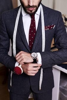 Hübscher schneider, der maßgeschneiderten anzug trägt