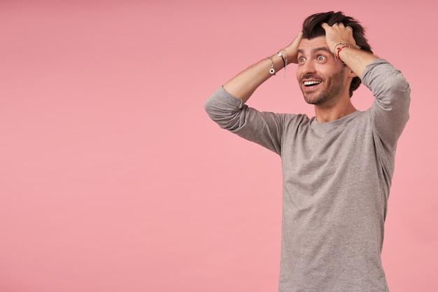 Hübscher schockierter bärtiger junger mann mit dunklem haar, grauem pullover tragend, mit weit geöffneten augen stehend, beiseite schauend und kopf mit händen haltend, als ob er nicht an nachrichten glaubt