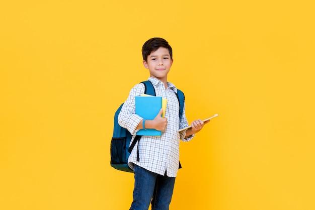 Hübscher schüler mit rucksack, der bücher und tablet-computer hält