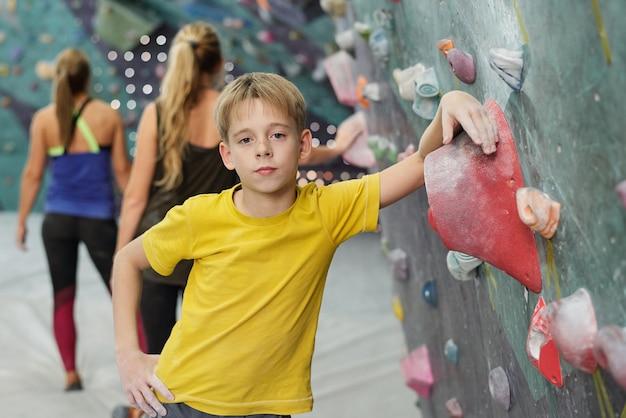 Hübscher schuljunge in der aktivkleidung stehend, während er durch kletterausrüstung mit frauen hinter sich gelehnt wird