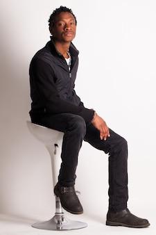 Hübscher schwarzer kerl, der auf einem stuhl sitzt