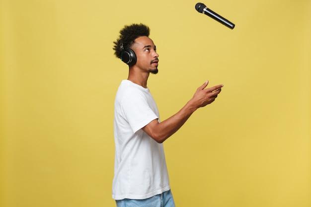 Hübscher schwarzer mann, der ein mikrofon wirft und singt.
