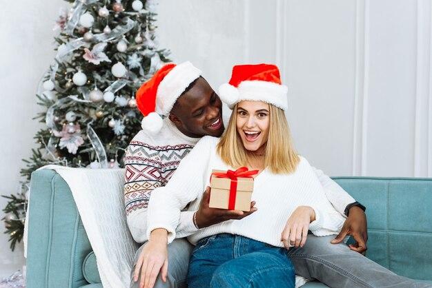 Hübscher schwarzer mann, der eine kaukasische frau mit einem weihnachtsgeschenk überrascht. gemütliche momente für einen winterurlaub. saisonale grüße konzept. eine frau ist überrascht von dem geschenk, das ihr mann ihr gemacht hat.