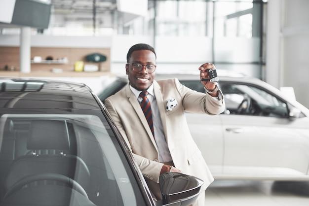 Hübscher schwarzer mann im autohaus umarmt sein neues auto und lächelt