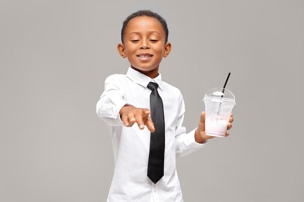 Hübscher schwarzer schuljunge, der hemd und krawatte trägt, die transparentes plastikglas hält, das gesunden energetischen proteinmilchshake trinkt, der glücklichen erfreuten gesichtsausdruck hat. gesundheit und essen