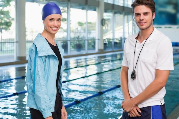 Hübscher schwimmer, der an der kamera durch das pool mit ihrem trainer lächelt