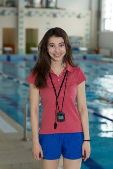 Hübscher schwimmtrainer, der am pool im freizeitzentrum steht.
