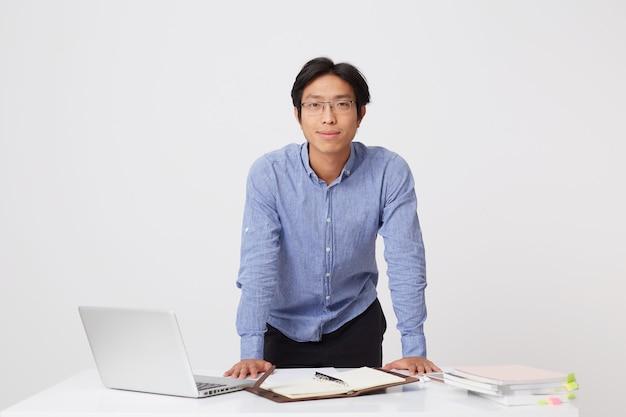 Hübscher selbstbewusster asiatischer junger geschäftsmann in den gläsern, die videogespräch unter verwendung des laptops und der kopfhörer über weißer wand haben