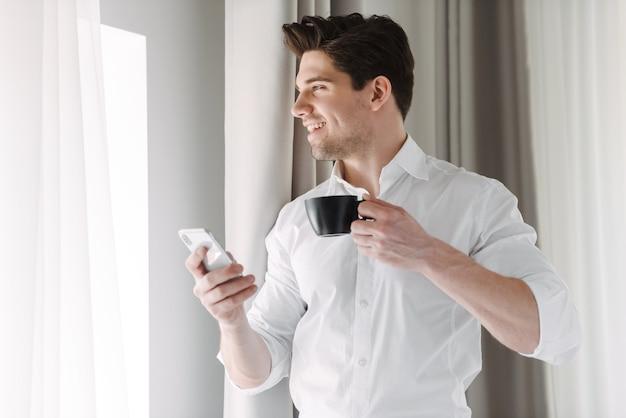 Hübscher selbstbewusster geschäftsmann, der drinnen am fenster steht und handy beim trinken der tasse kaffee verwendet