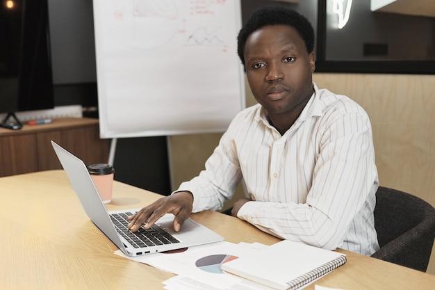 Hübscher selbstbewusster junger dunkelhäutiger mann, der mit papieren am schreibtisch sitzt