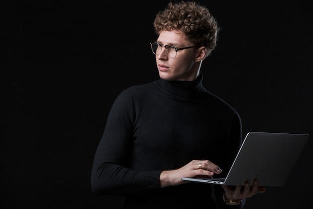 Hübscher selbstbewusster junger geschäftsmann mit lockigen haaren mit rollkragen, der vor einer isolierten wand steht und an einem laptop arbeitet