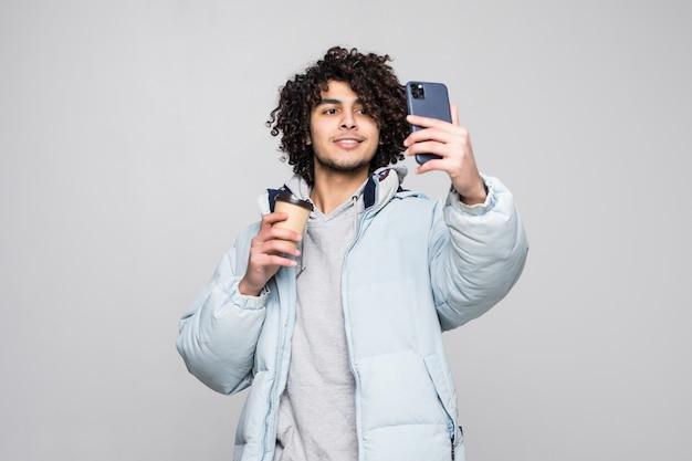 Hübscher, selbstbewusster junger lockiger mann, der ein selfie nimmt und tasse des kaffee zum mitnehmen hält, der lokal über grauer wand steht