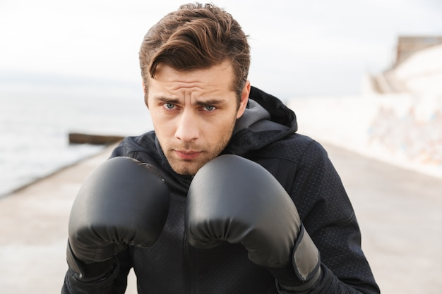 Hübscher selbstbewusster junger sportler, der am strand trainiert und boxübungen macht