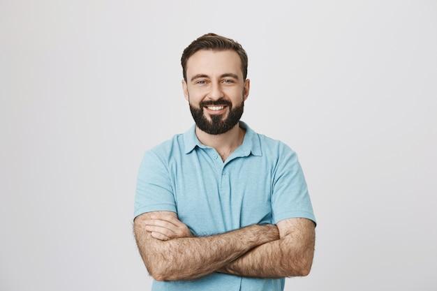 Hübscher selbstbewusster lächelnder mann mit gekreuzten händen auf der brust