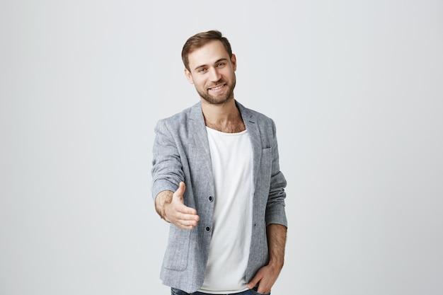 Hübscher selbstbewusster mann strecken hand für händedruck