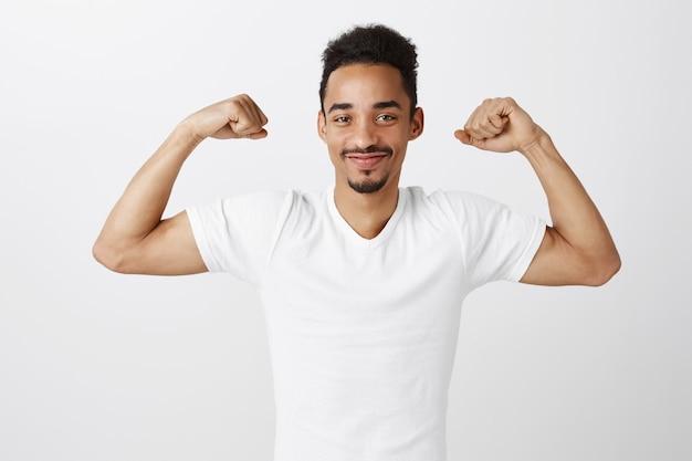 Hübscher selbstbewusster und starker afroamerikaner, der bizeps biegt, training im fitnessstudio, frech aussehend