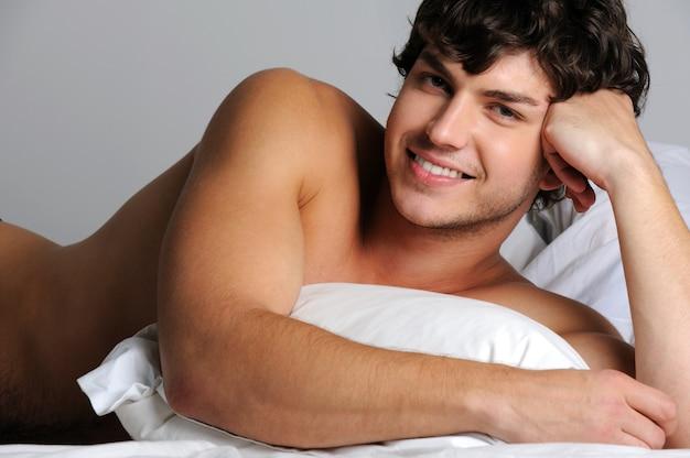 Hübscher sexy lächelnder junger mann, der im bett mit kissen liegt
