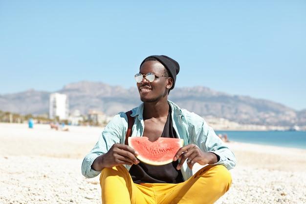 Hübscher sorgloser männlicher student, der auf kieselstrand mit scheibe wassermelone sitzt
